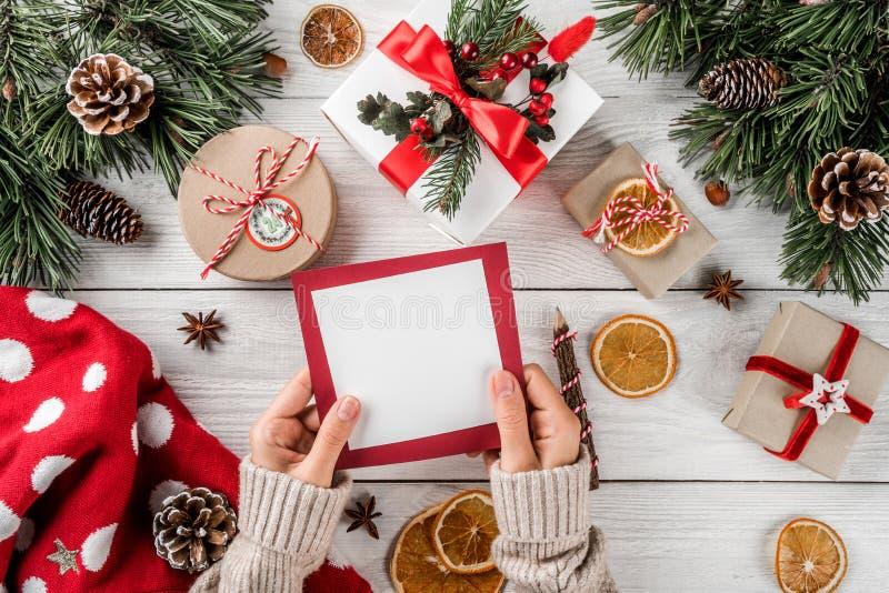 拿着信件的女性手对在白色木背景的圣诞老人与圣诞礼物,冷杉分支,毛线衣,杉木锥体 免版税库存图片
