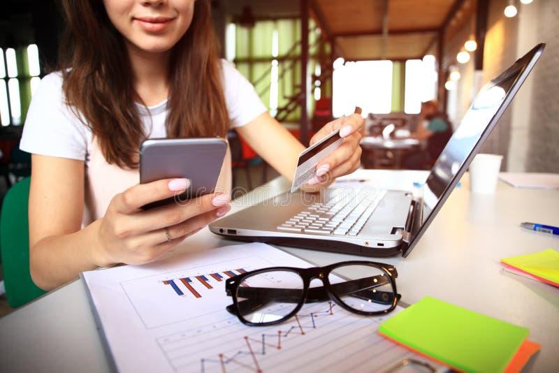 拿着信用卡和使用便携式计算机的少妇 在线购物概念 免版税库存照片