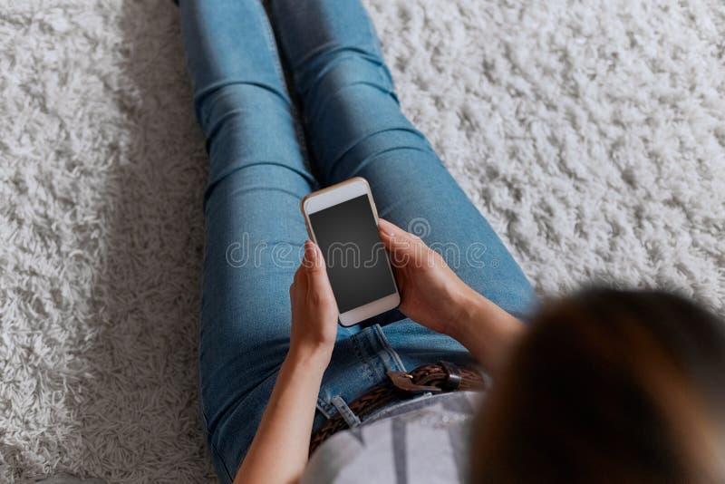 拿着信用卡和使用在地板上的年轻女人电话开会 ?? E 库存图片