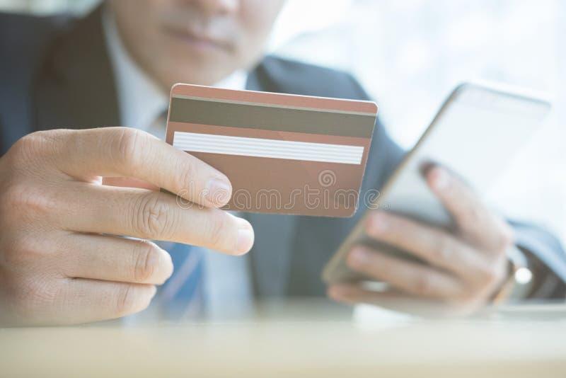拿着信用卡和使用巧妙的手机的男性为onli 库存照片