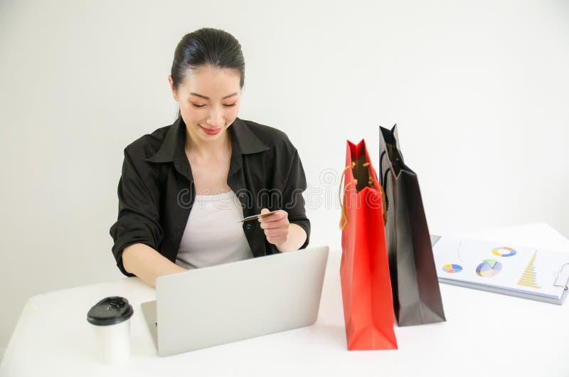 拿着信用卡和使用手提电脑的年轻女人 E 免版税图库摄影