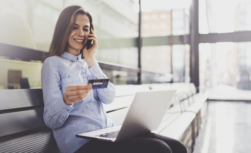 拿着信用卡和使用智能手机和流动膝上型计算机的年轻可爱的女实业家在女性手上,当坐时 免版税库存图片