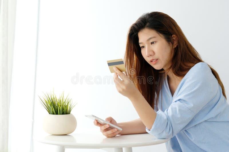 拿着信用卡和使用智能手机的年轻亚裔妇女为购物网上,企业和技术概念,网上付款, 免版税图库摄影