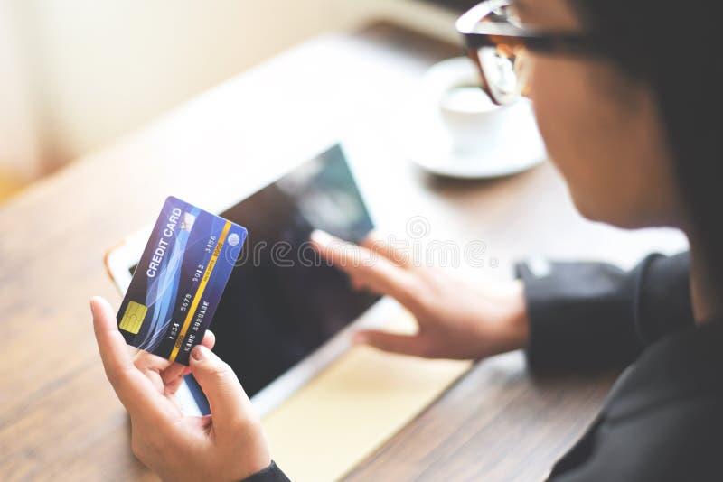 拿着信用卡和使用片剂的妇女手为网络购物在办公室桌咖啡杯背景中-工作者 免版税图库摄影