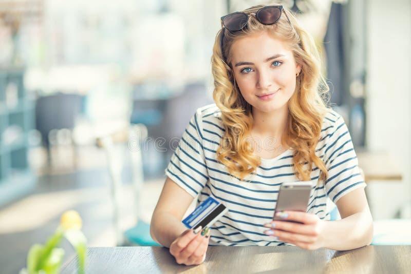 拿着信用卡和使用细胞,网络购物的智能手机的咖啡馆的年轻女人 免版税库存照片
