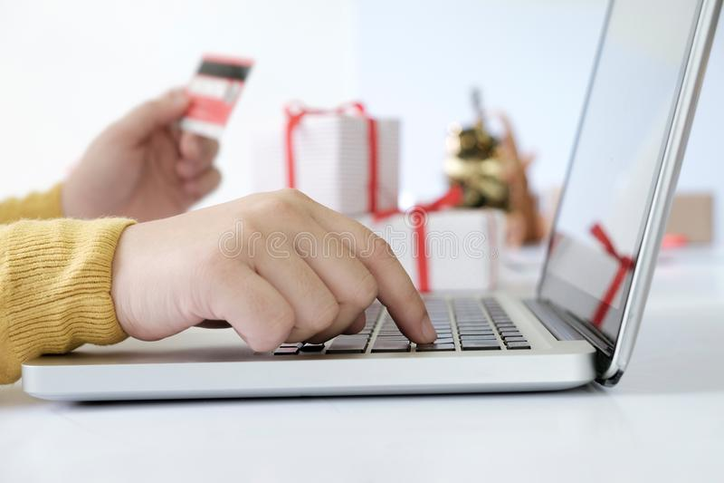 拿着信用卡和做在网上购物的妇女 免版税库存图片