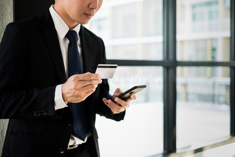拿着信用卡和在网上使用膝上型计算机和智能手机购物网站的人,购物的概念 免版税库存照片