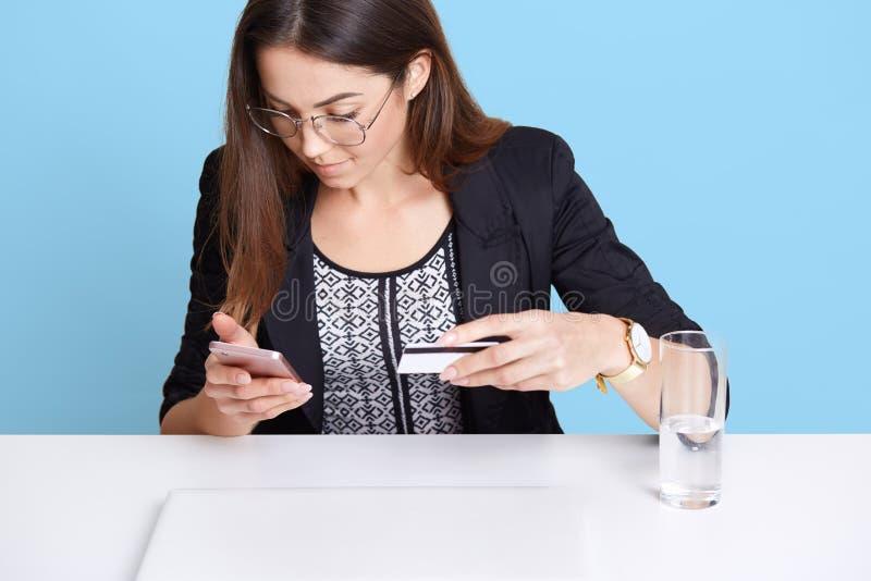 拿着信用卡和她的智能手机的女孩,付网上付款使用无线互联网,坐在的女性穿戴的黑成套装备 免版税库存图片