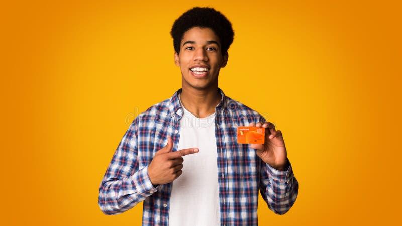 拿着信用卡和点对此的愉快的非裔美国人的人 免版税库存图片