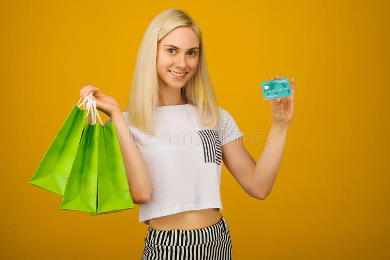拿着信用卡和绿色购物带来的愉快的年轻美丽的白肤金发的妇女特写镜头画象,看照相机,被隔绝 库存照片