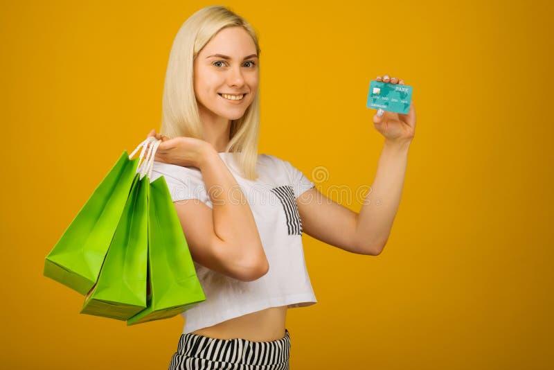 拿着信用卡和绿色购物带来的愉快的年轻美丽的白肤金发的妇女特写镜头画象,看照相机,被隔绝 免版税库存照片