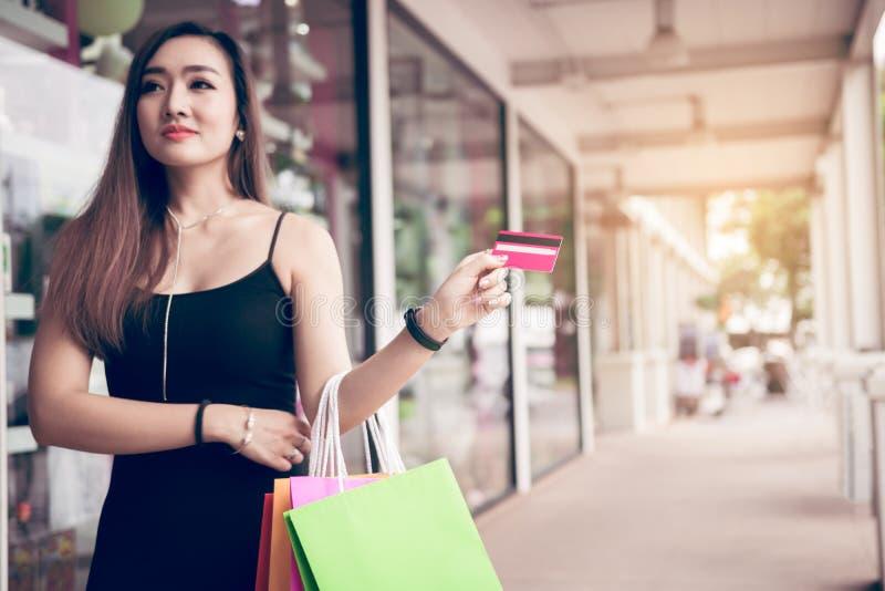 拿着信用卡和购物带来的妇女的接近的手在购物中心 免版税图库摄影