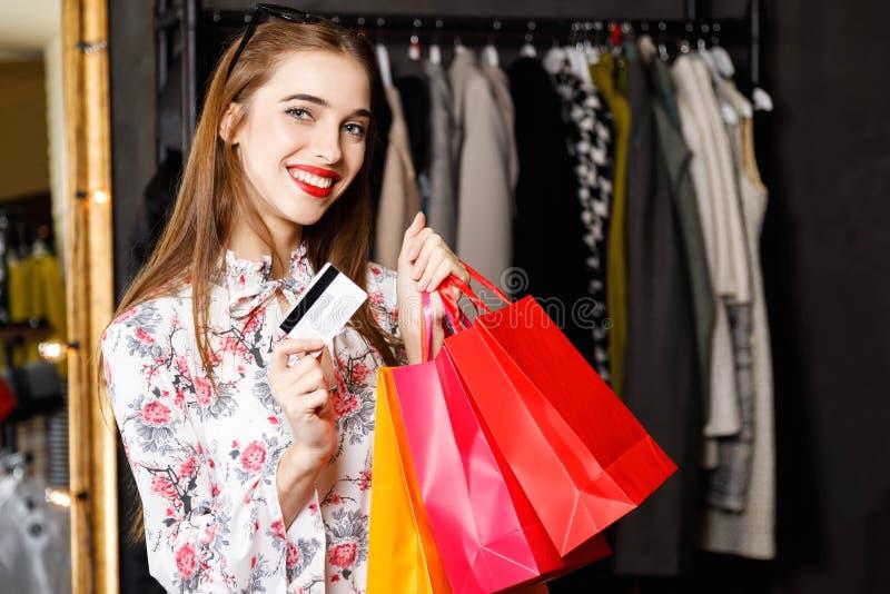拿着信用卡和购物袋的俏丽的微笑的妇女 免版税图库摄影