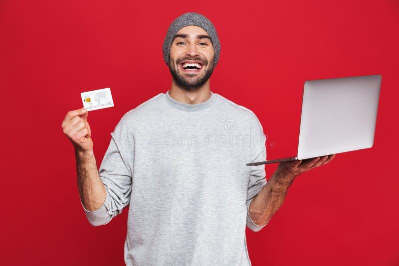 拿着信用卡和银色膝上型计算机的愉快的人照片被隔绝在红色背景 免版税库存照片