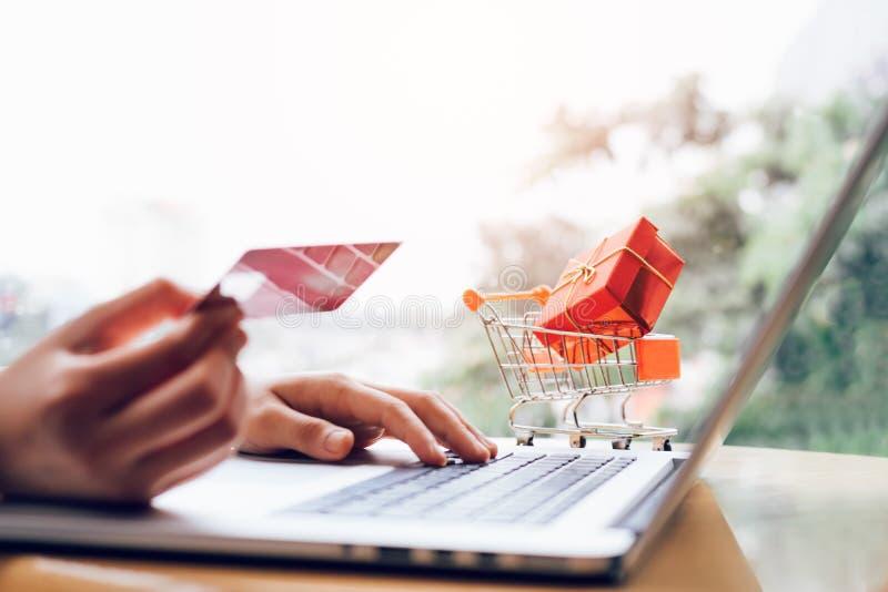 拿着信用卡和键入键盘膝上型计算机的妇女做shopp 免版税库存照片