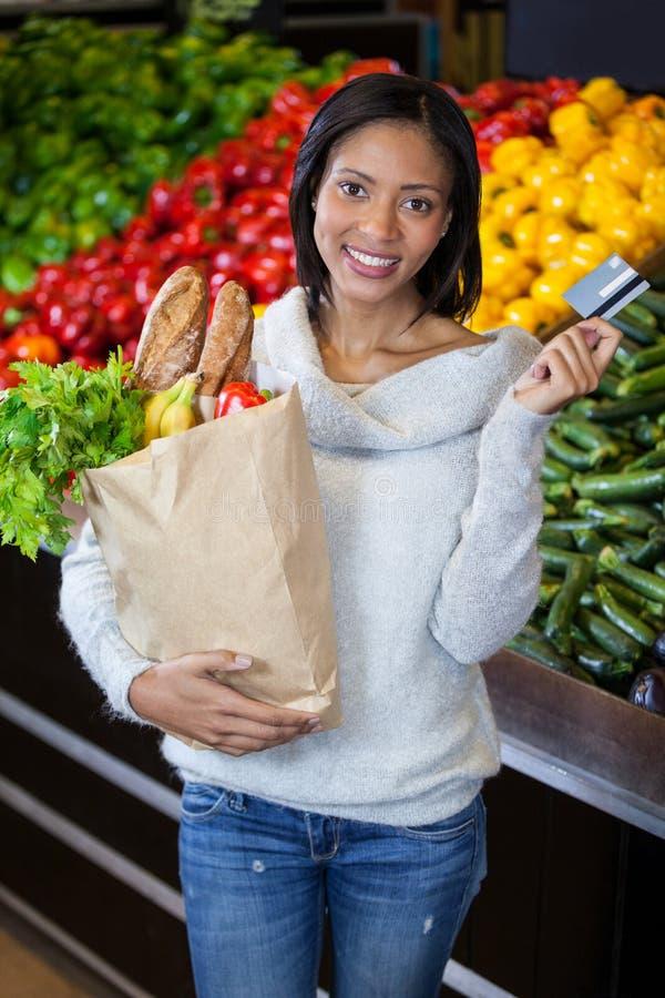 拿着信用卡和食品杂货袋的妇女 图库摄影