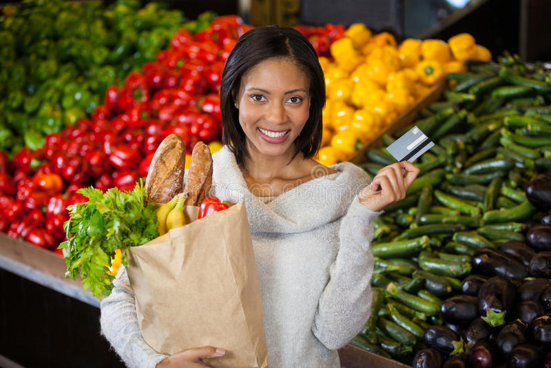 拿着信用卡和食品杂货袋的妇女 免版税库存图片