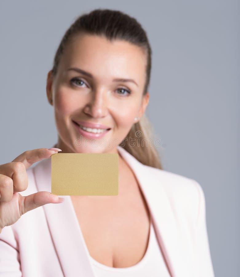 拿着信用卡的女商人反对她的面孔被隔绝 免版税库存图片