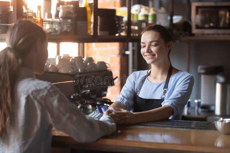 拿着信用卡的女性付帐使用NFC现代技术 图库摄影