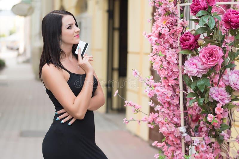 拿着信用卡的妇女在花店前 免版税库存照片