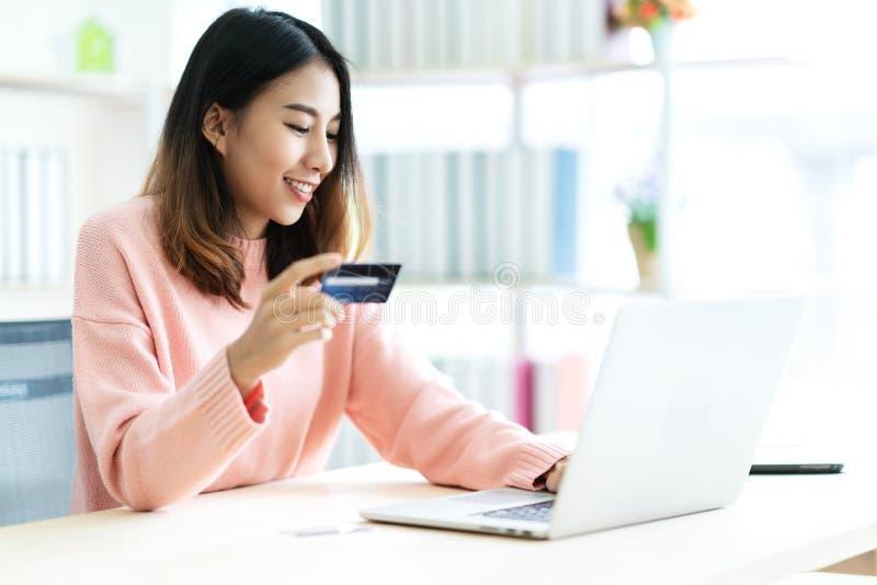拿着信用卡的年轻可爱的亚裔妇女坐在桌键入的键盘在便携式计算机对在网上购物 免版税库存图片