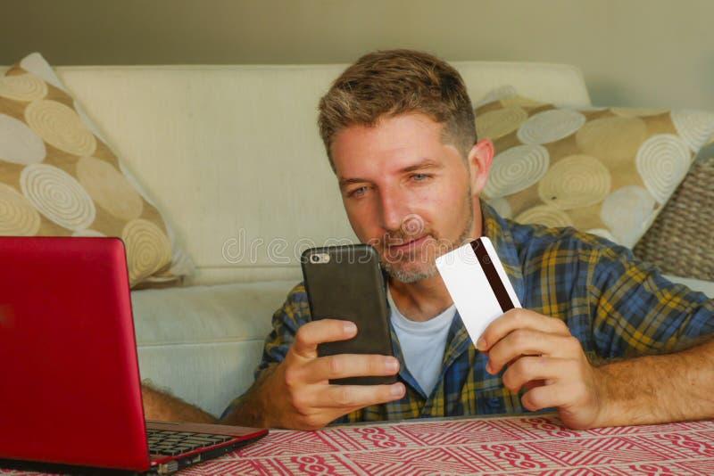 拿着信用卡的年轻英俊和愉快的人在家坐沙发长沙发使用手提电脑和手机网络购物 免版税库存图片