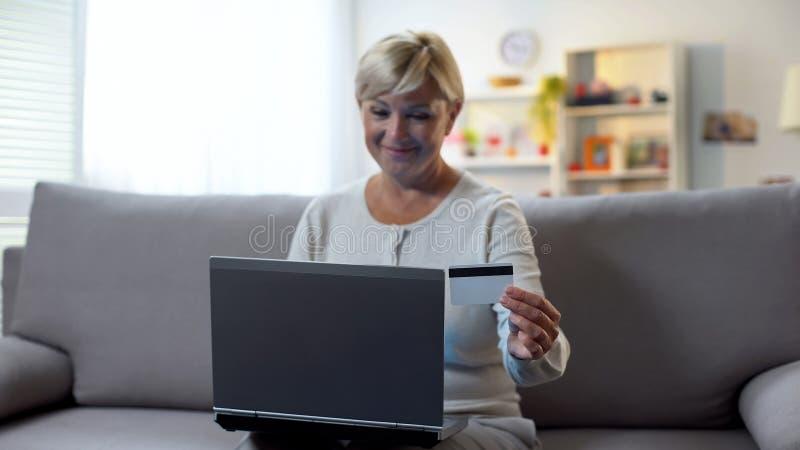 拿着信用卡的微笑的妇女使用膝上型计算机,预定的机票,假期 免版税图库摄影