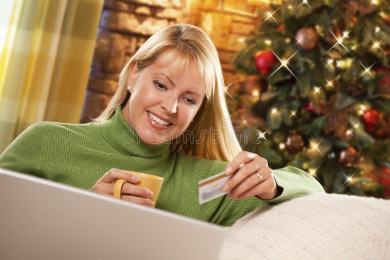 拿着信用卡的白肤金发的妇女使用膝上型计算机在圣诞树附近 免版税库存图片