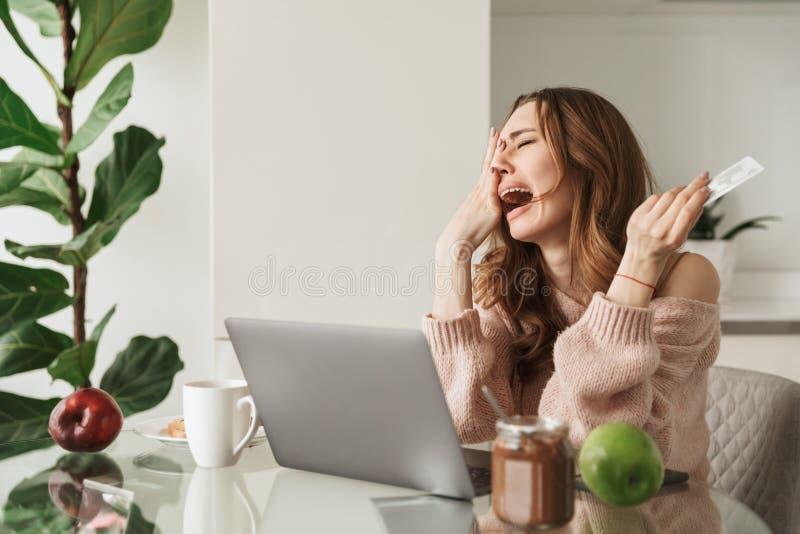 拿着信用卡的翻倒少妇的画象 免版税库存图片