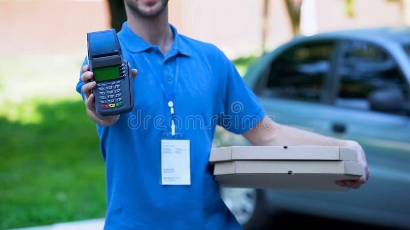 拿着信用卡终端,付款技术,服务的男性薄饼传讯者 免版税库存图片