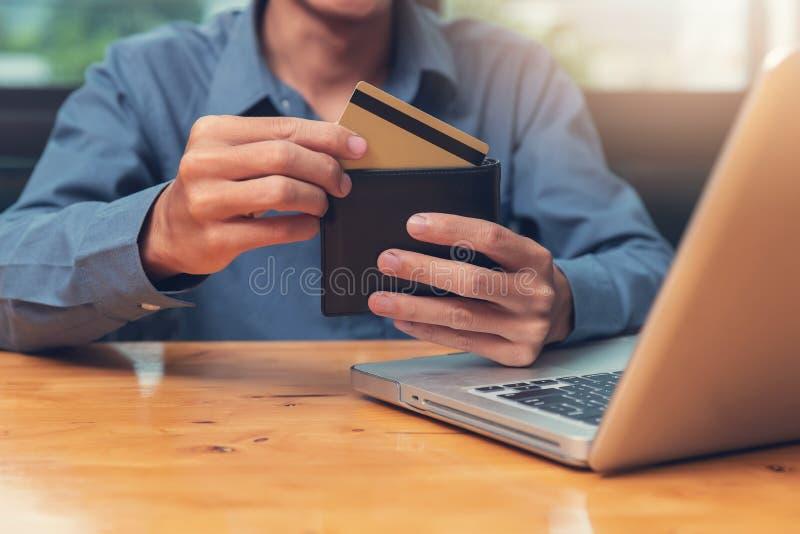 拿着信用推车的商人对在网上购物与在咖啡馆的计算机膝上型计算机 库存照片