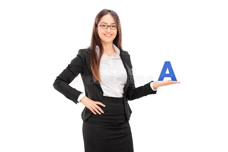 拿着信件A的年轻女性学校教师 免版税库存照片