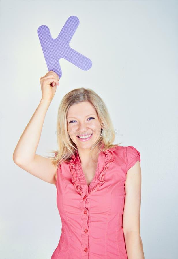 拿着信件K的微笑的妇女 免版税库存照片