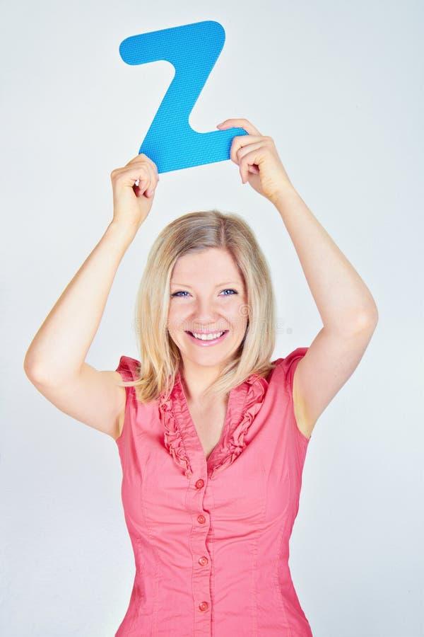 拿着信件Z的微笑的妇女 免版税库存照片