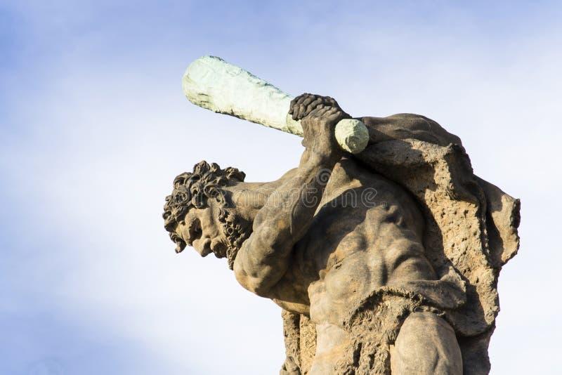 拿着俱乐部的战斗机雕象的特写镜头看下来与蓝天在背景中 免版税库存图片