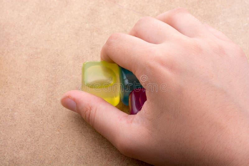 拿着假五颜六色的冰块的手 免版税库存照片