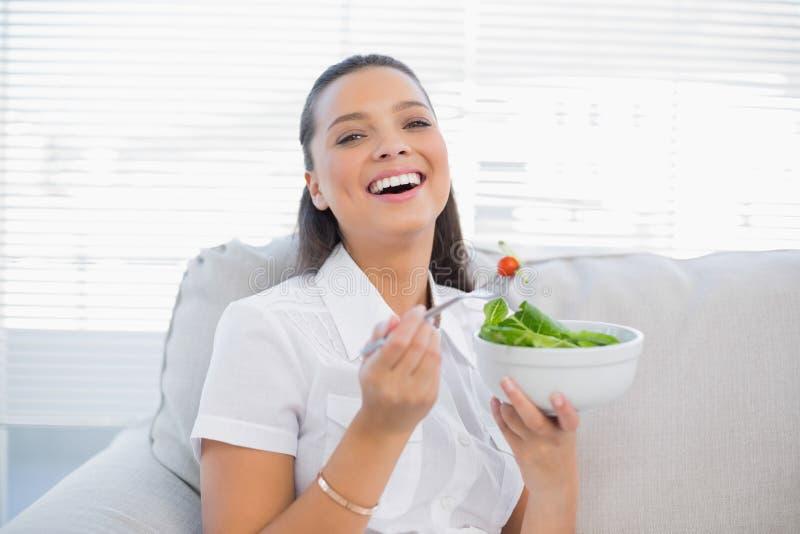 拿着健康沙拉的快乐的俏丽的妇女坐沙发 免版税图库摄影