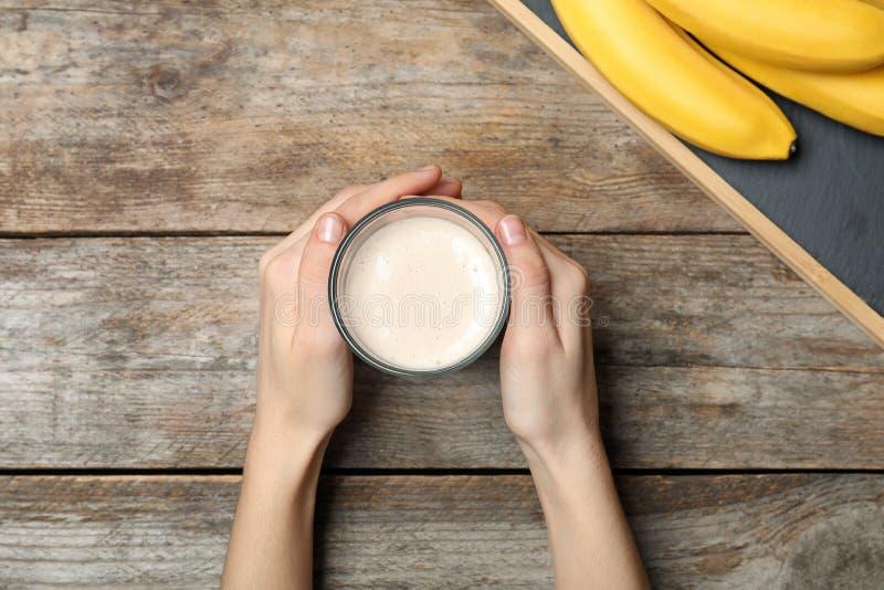 拿着健康蛋白质震动的玻璃妇女靠近香蕉在木桌上 图库摄影