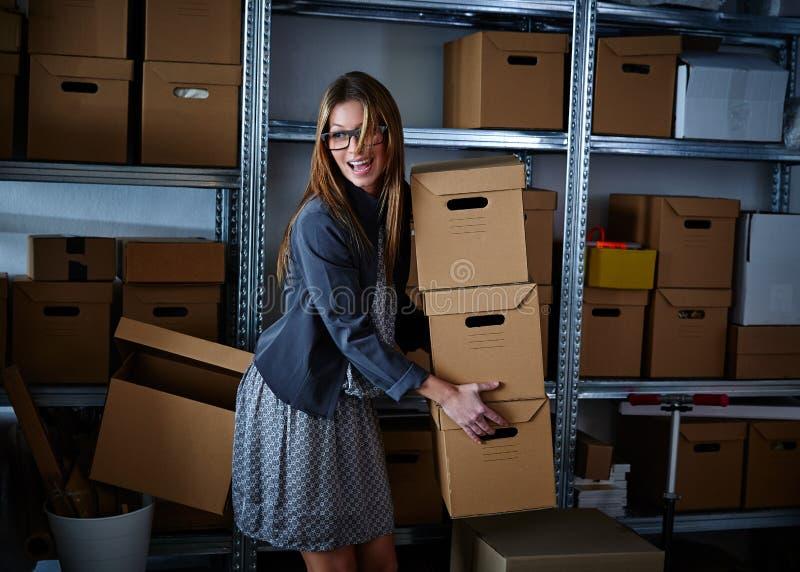 拿着储藏盒的滑稽的女实业家 免版税库存图片