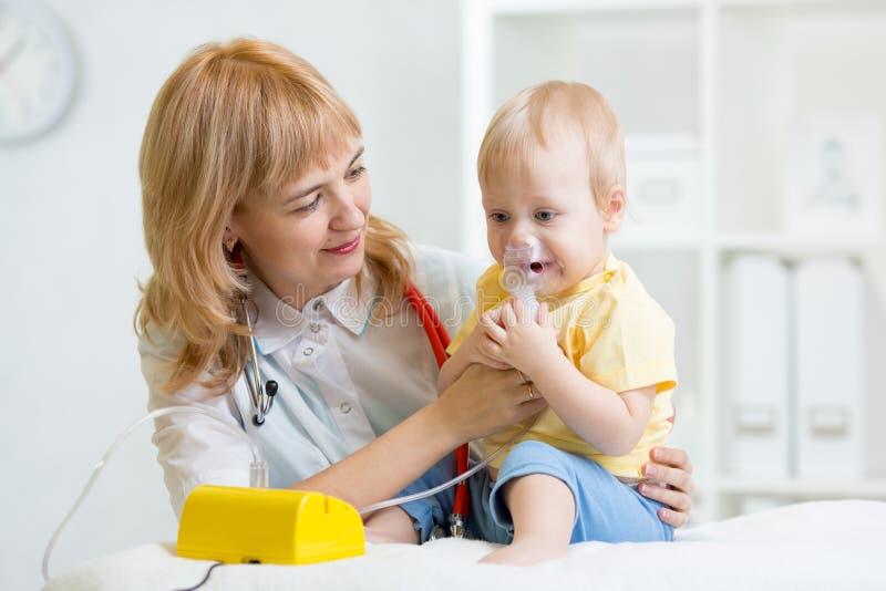 拿着儿童呼吸的医生吸入器面具 库存照片