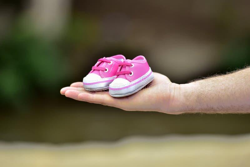 拿着儿童的鞋子的手 免版税库存照片