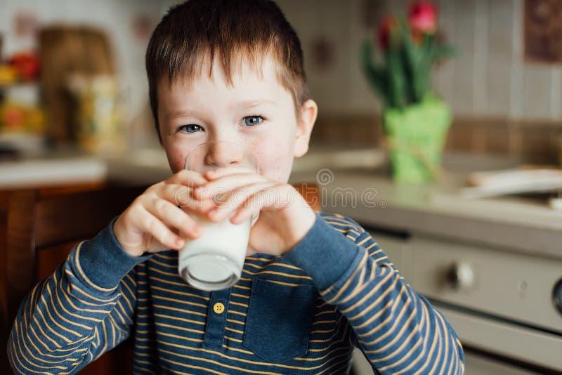 拿着充分的杯牛奶的小男孩坐在厨房用桌上 图库摄影