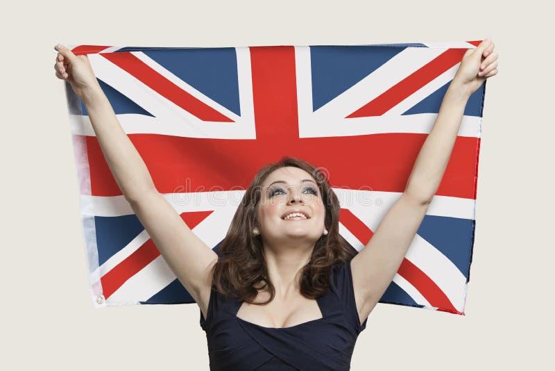 拿着充满自豪感的少妇英国旗子在灰色背景 免版税库存图片