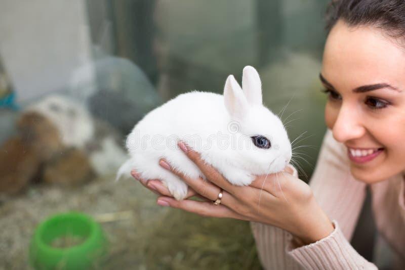 拿着兔子的女孩在宠物店 免版税库存图片