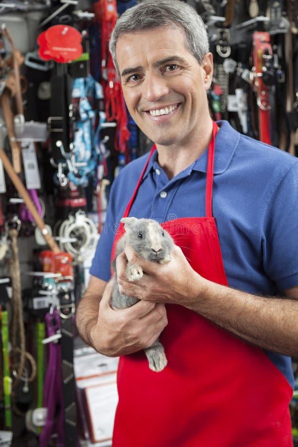 拿着兔子的确信的成熟推销员在宠物商店 库存图片