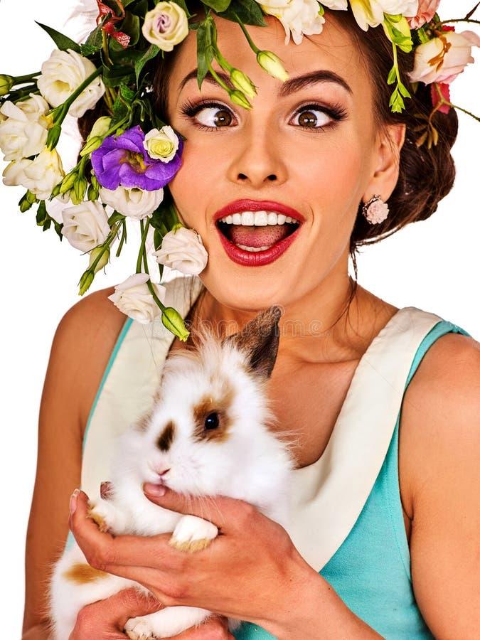 拿着兔宝宝的复活节女孩 有假日春天的妇女开花发型 免版税库存照片