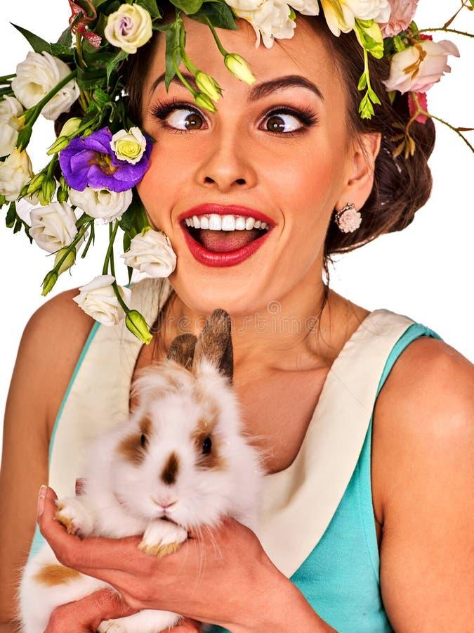 拿着兔宝宝的复活节女孩 有假日春天的妇女开花发型 免版税库存图片