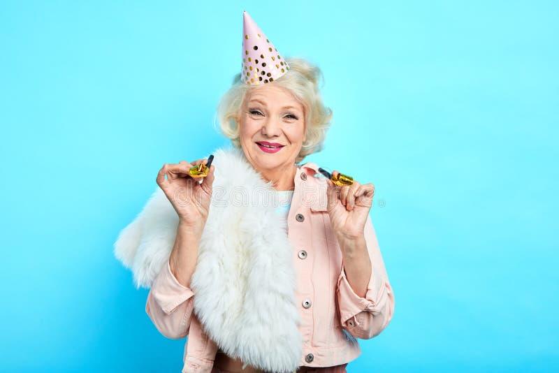 拿着党垫铁和看照相机的快乐的宜人的俏丽的老妇人 库存图片