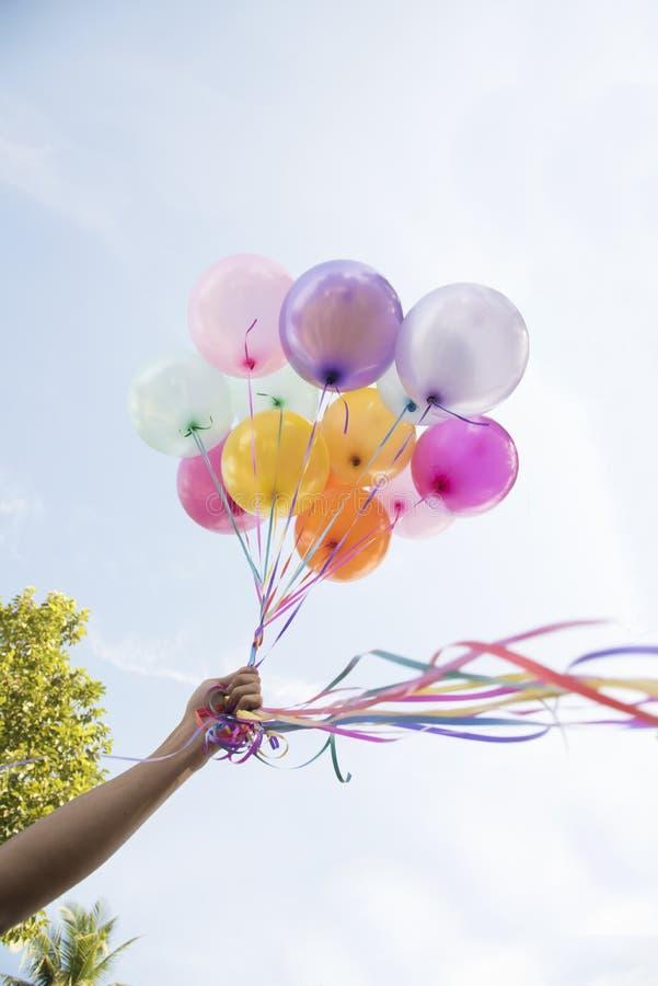拿着党节日的妇女手五颜六色的气球 免版税图库摄影