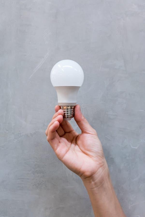 拿着全新的白色LED电灯泡的妇女手 免版税库存照片
